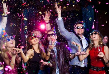 Cheerful young people showered with confetti on a club party.
